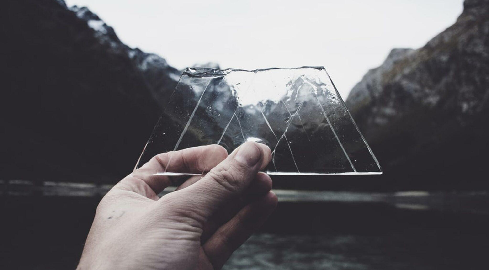 Jemand hält ein bergförmiges Stück Eis vor Berge und einen See.