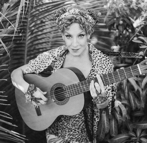 Schwarz-Weiß-Bild von Sissi Perlinger mit Gitarre.
