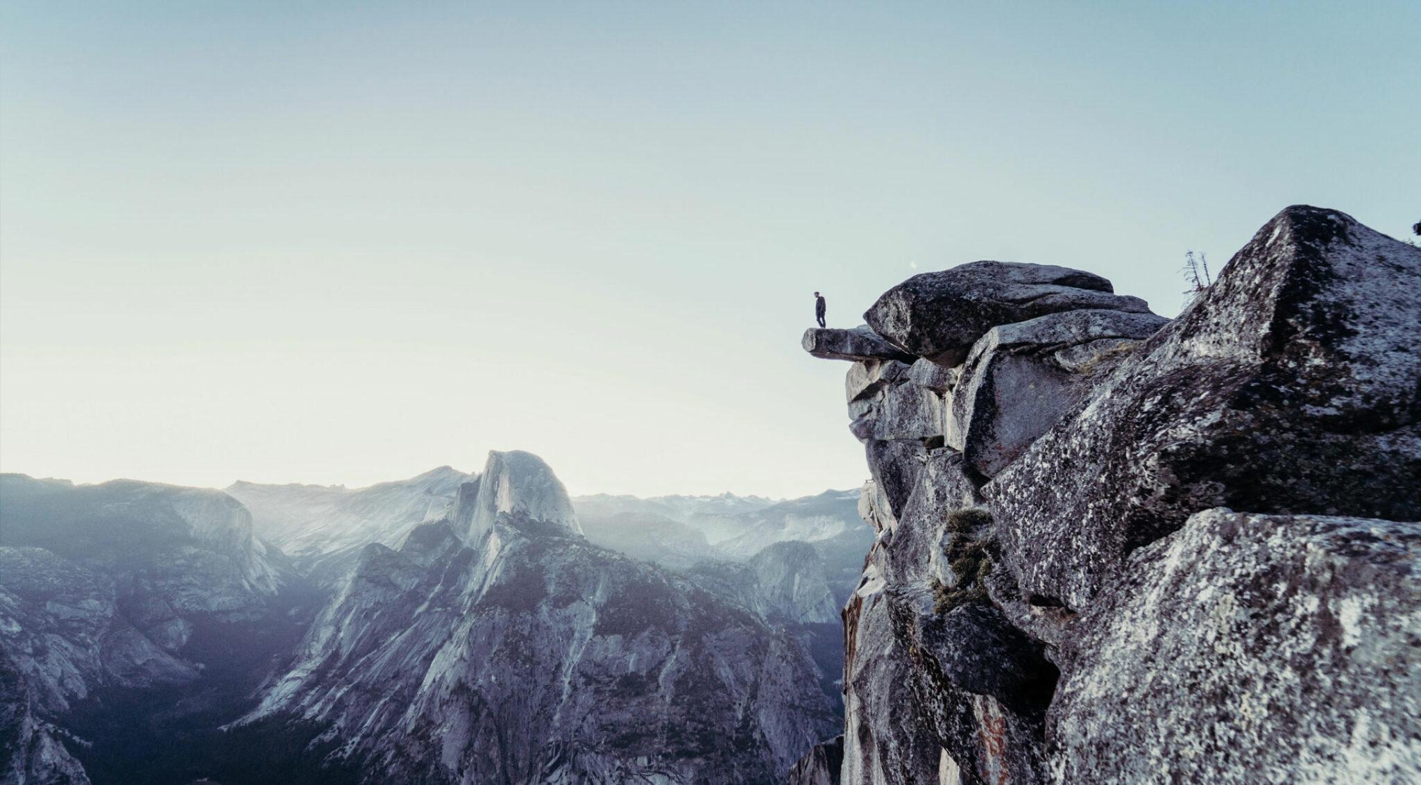 Umgeben von Gebirge steht eine Person auf einem Felsvorsprung.