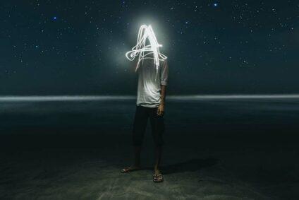Ein Mann vor dunklem Hintergrund mit leuchtenden Strichen vor dem Gesicht.