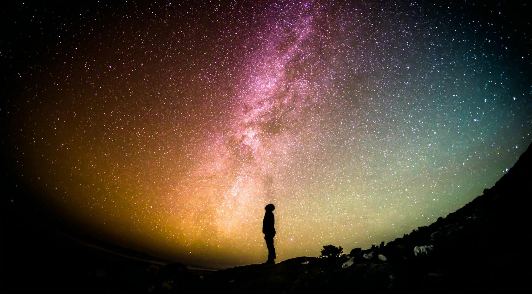Eine Person vor dem Sternenhimmel.