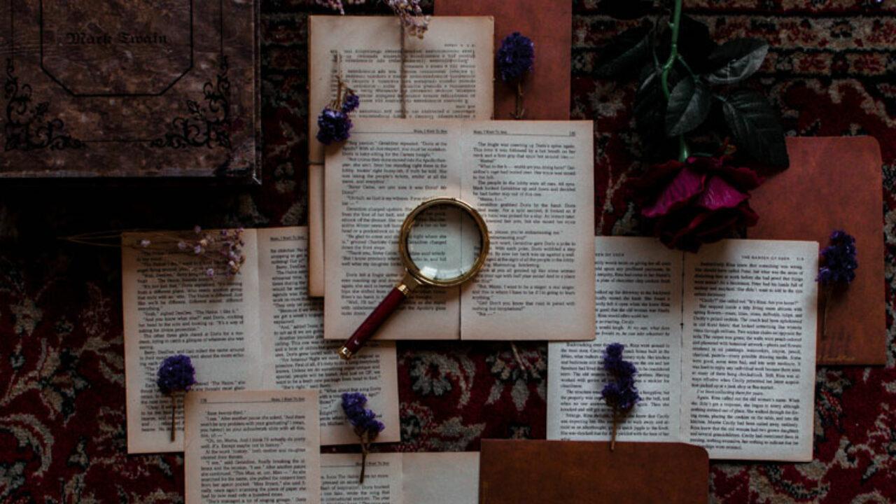 Bücher und eine Lupe liegen auf einem rot gemusterten Teppich.