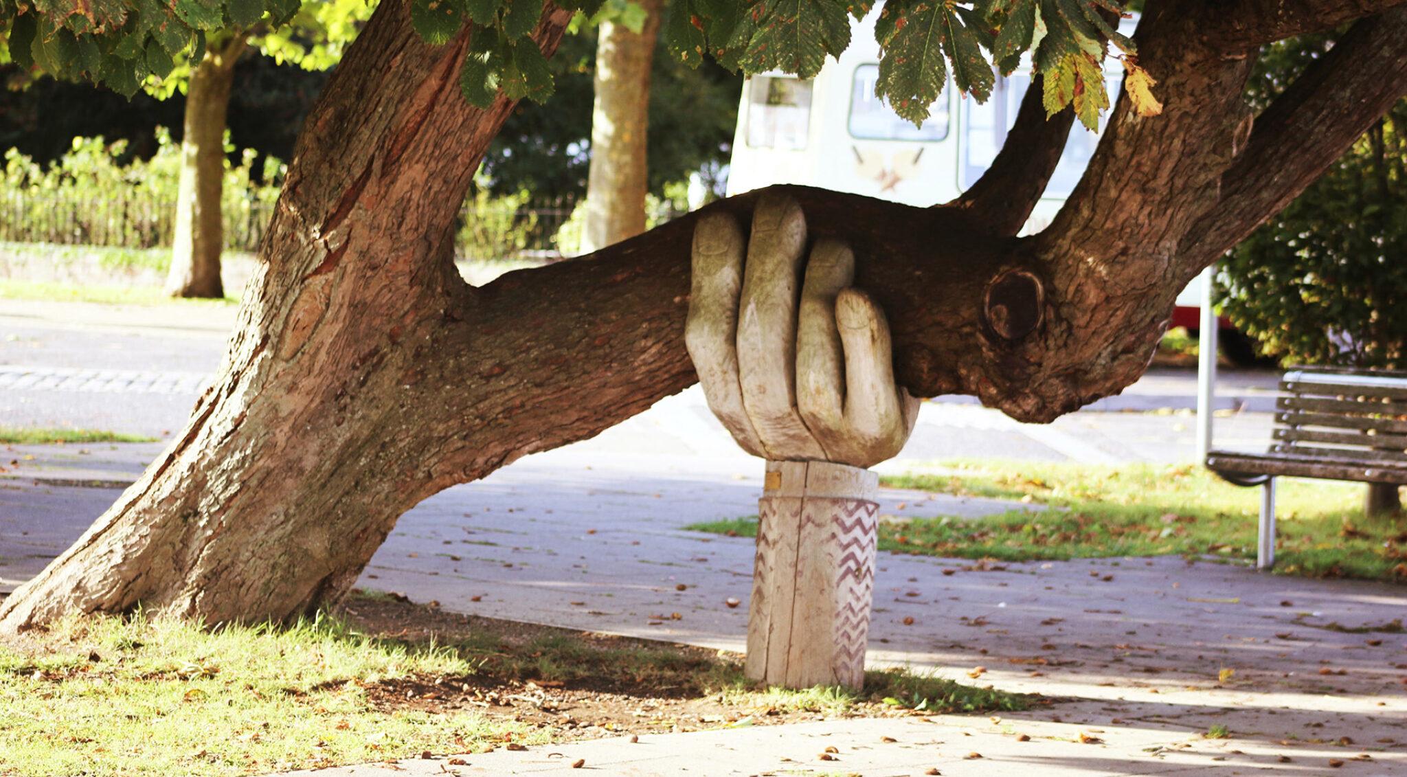 Eine Hand aus Holz hält den großen Ast eines Baumes.