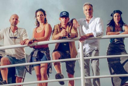 """Die Crew des Filmes """"Retter der Meere"""" an der Schiffsreling."""