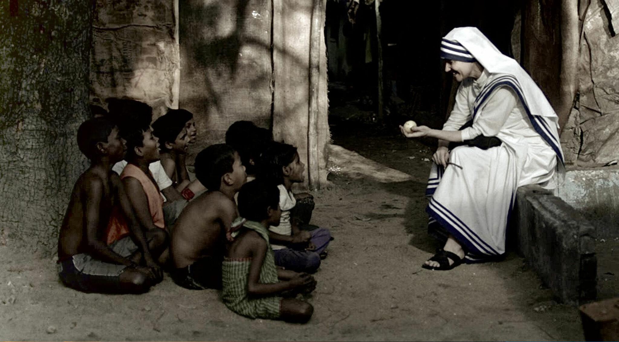 Mutter Teresa mit Straßenkindern.