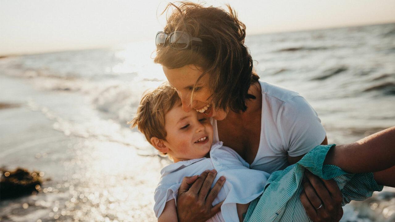 Eine Frau hält ihren Sohn am Meer im Arm.