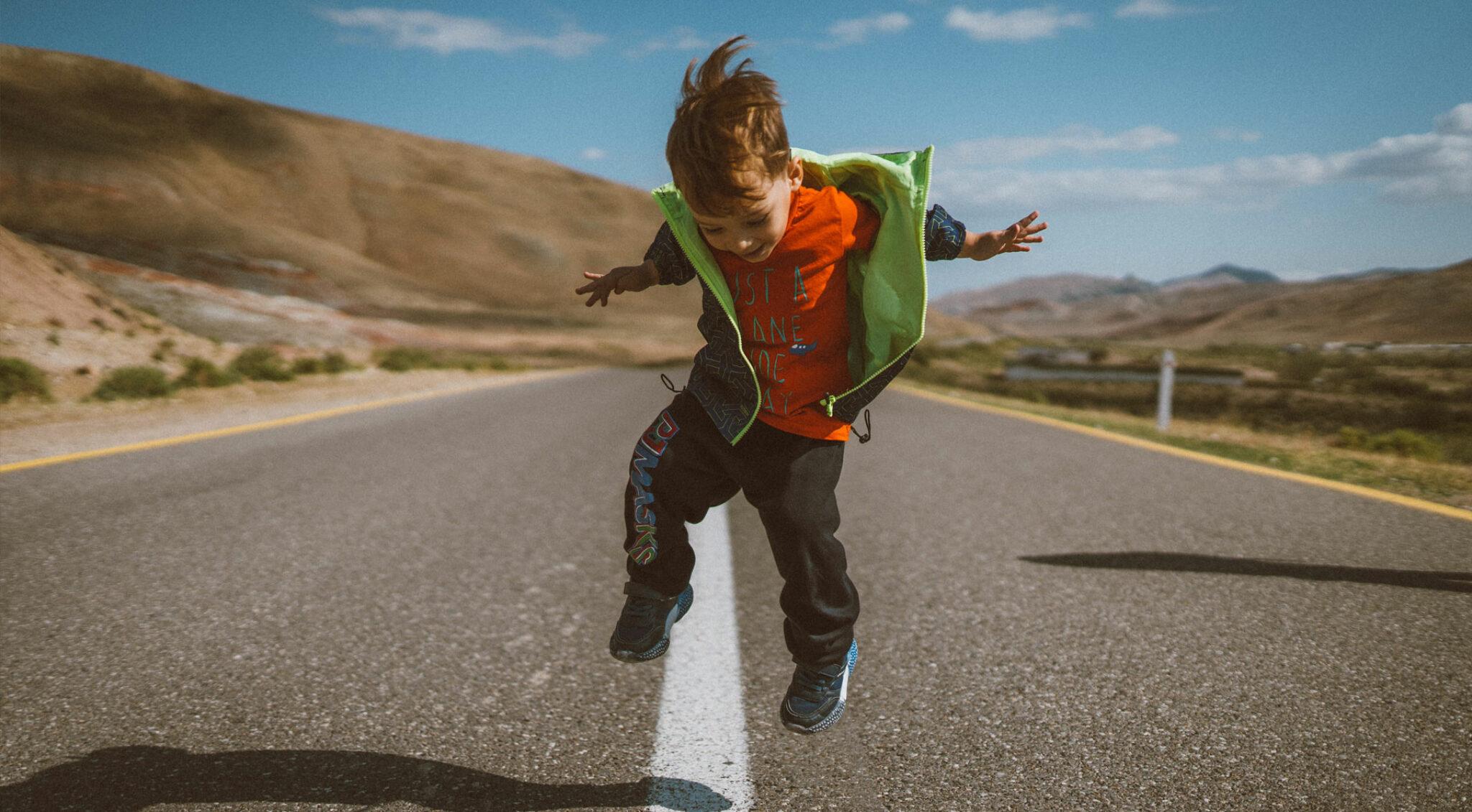 Ein Junge springt auf einer leeren Straße in die Luft.