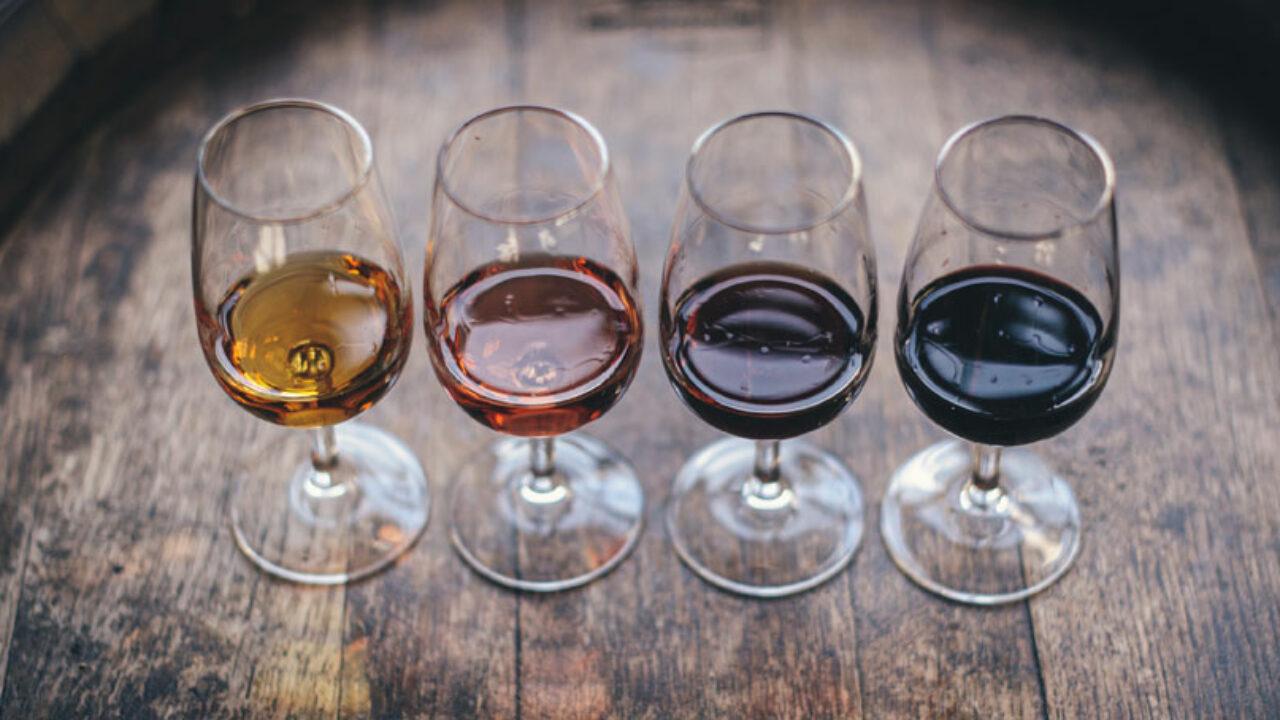 Vier Weingläser, gefüllt mit unterschiedlichen Weinen, nebeneinander auf einem Holztisch.