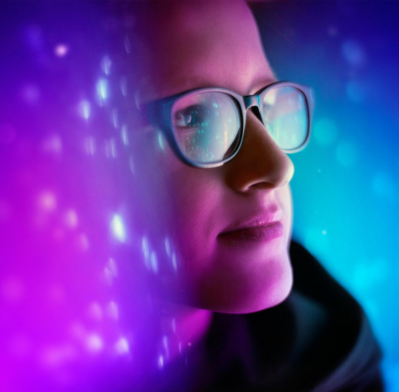 Frau mit Brille zwischen blau-lila beleuchteten Wänden.