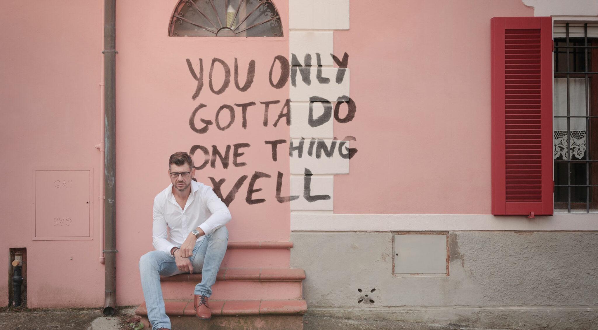 Henning Vöpel vor einer Wand mit der Aufschrift: You only gotta do one thing well.