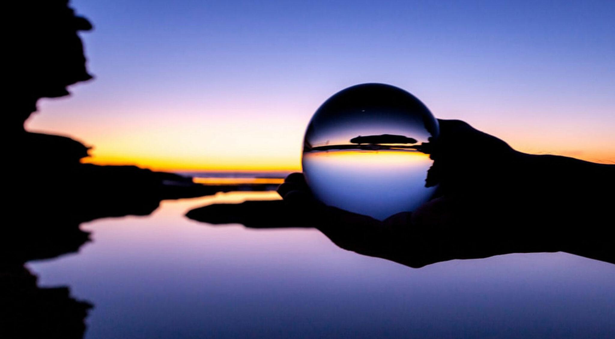 Jemand hält in der Abenddämmerung eine durchsichtige Kugel von eine Seenlandschaft.
