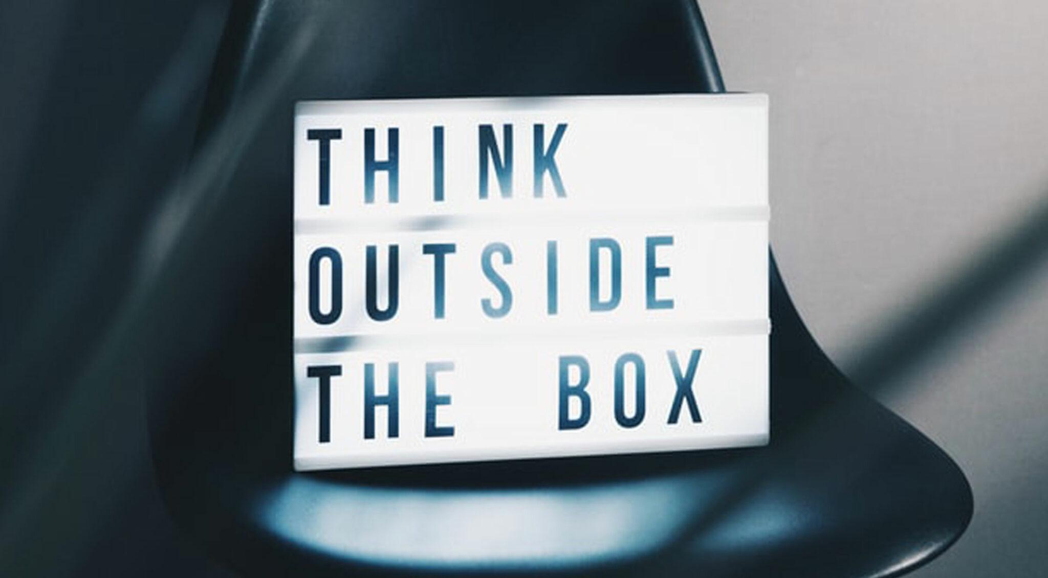 """Eine Lightbox mit dem Text """"Think outside the box"""" auf einem schwarzen Stuhl."""