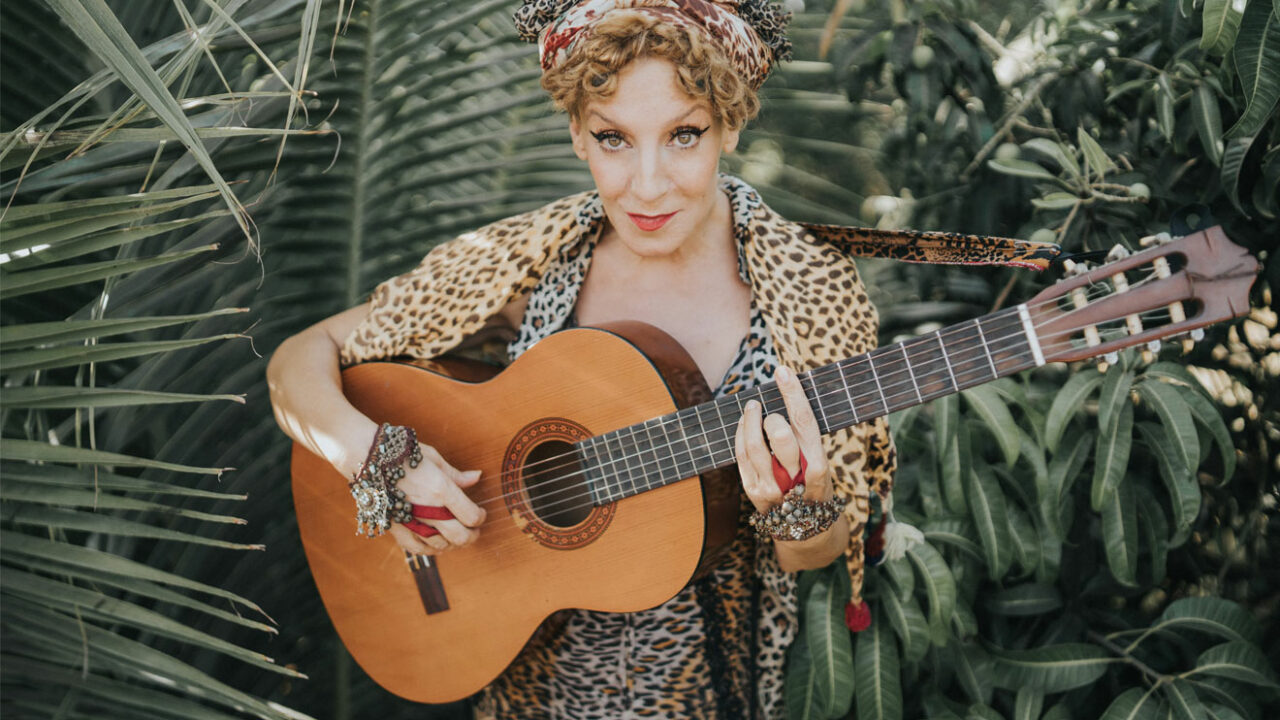 Sissi Perlinger mit Gitarre vor einem Hintergrund aus Pflanzen.