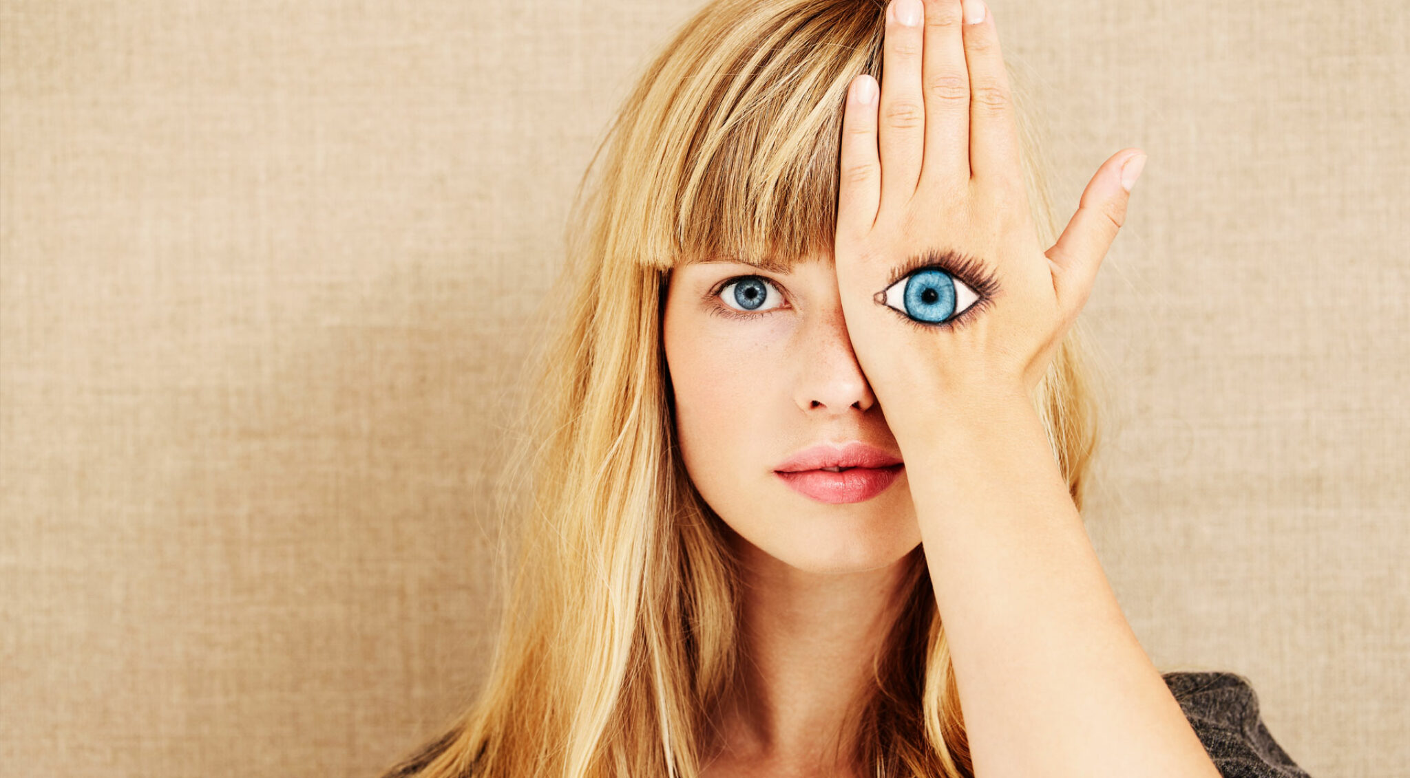 Eine Frau hält sich ihre Hand mit einem aufgemalten Auge vor das Gesicht.
