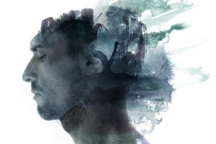 Das Gesicht eines Mannes wird überlagert von dunklen Farbklecksen.