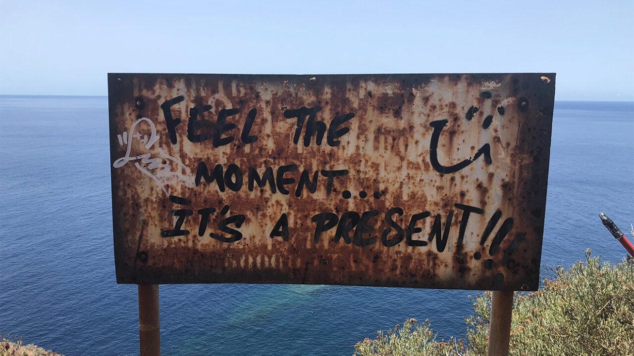 "Schild mit der Aufschrift ""Feel the moment... it's a present!""."