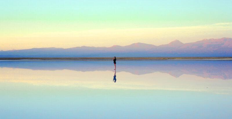 Person auf einer Fläche, die den bunten Horizont spiegelt.