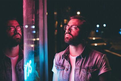 Junger Mann steht nachts vor einem Schaufenster und wird von rotem Neonlicht bestrahlt.
