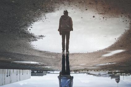 Umgedrehtes Bild einer Person, die sich in einer Pfütze spiegelt.