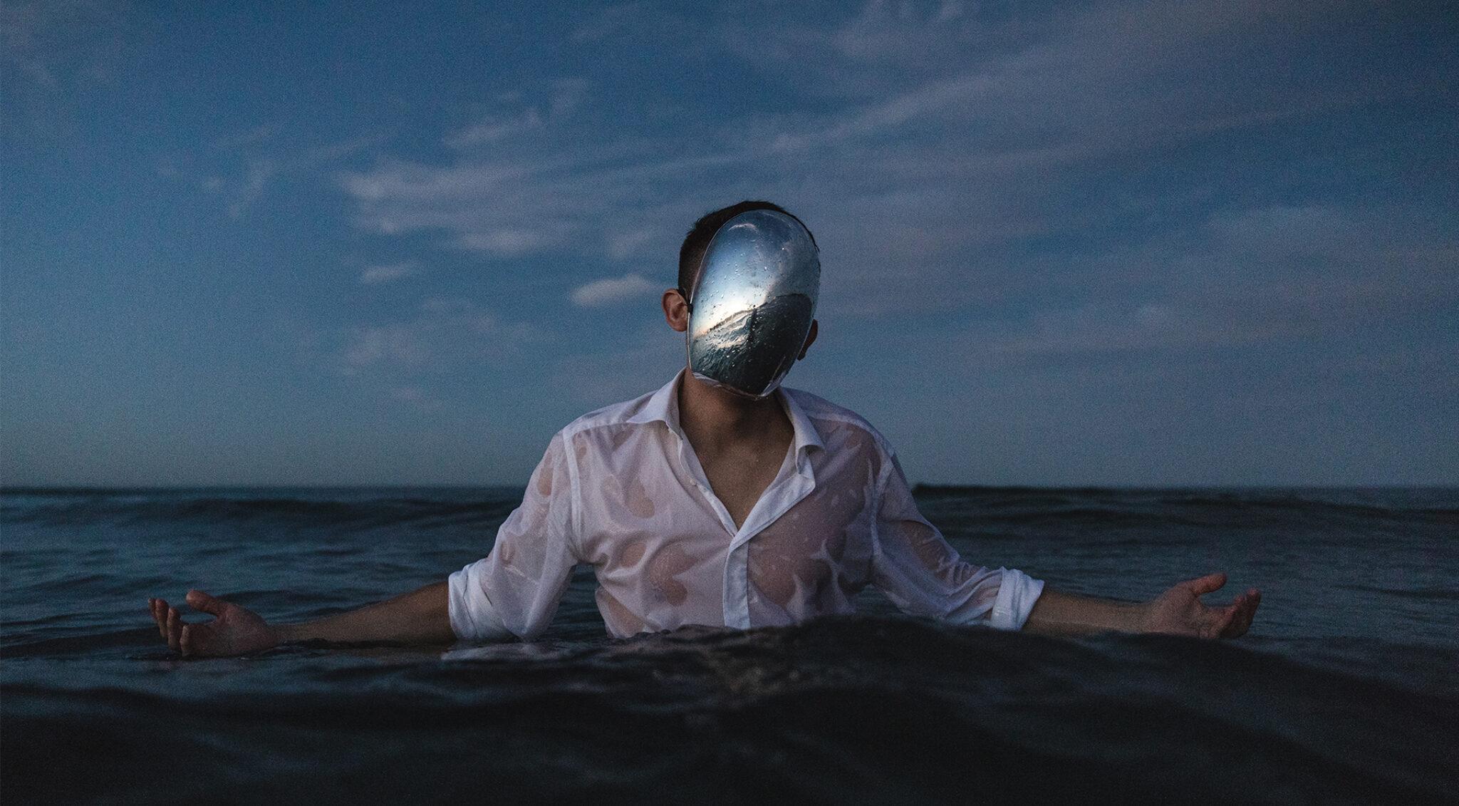 Ein Mann mit weißem Hemd steht bis zur Brust im Meer, vor dem Gesicht trägt er eine silberne Maske.