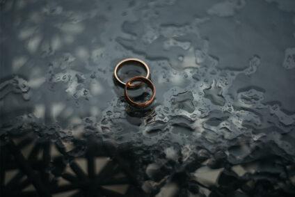 Zwei Ringe liegen auf feuchtem Boden.