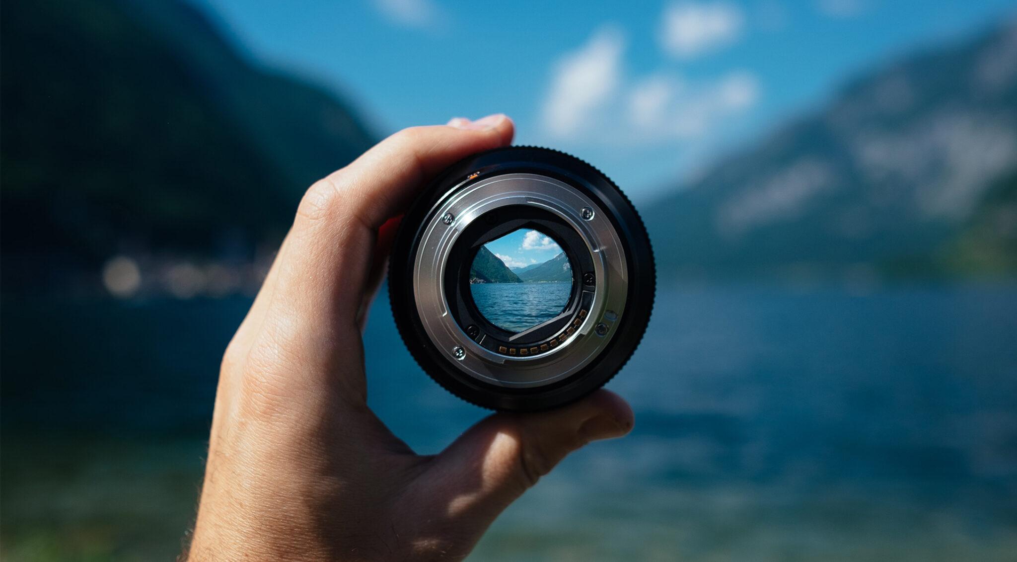 Blick in eine Kameralinse, die jemand vor einen See hält.