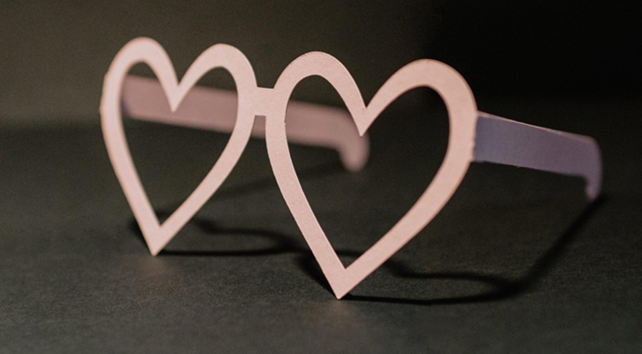 Eine aus rosa Papier gefertigte Brille mit Gläsern in Herzform.