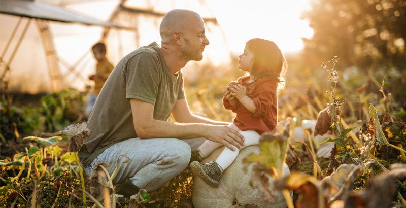 Ein Mann mit seiner Tochter auf einem Feld.