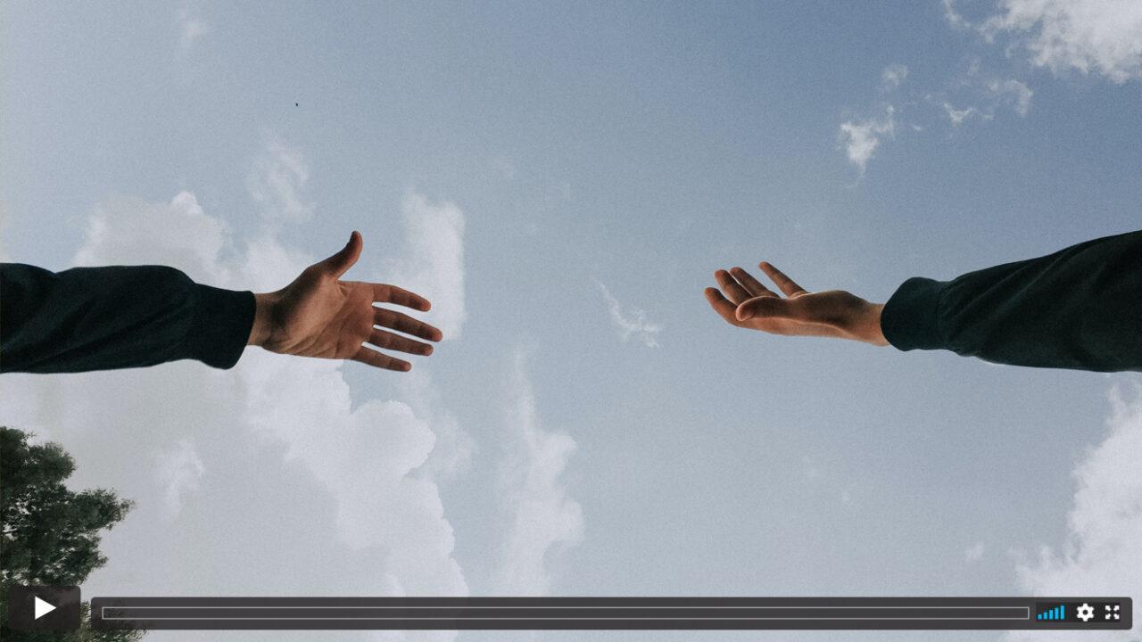 Zwei Arme vor blauem Himmel.