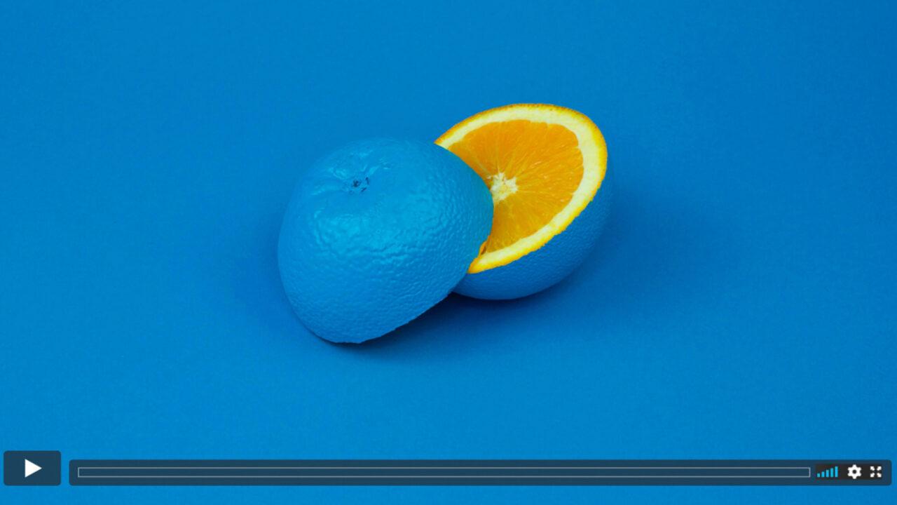 Halbierte Orange mit blau bemalter Schale vor blauem Hintergrund.