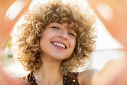 Lachende Frau mit blonden Locken.