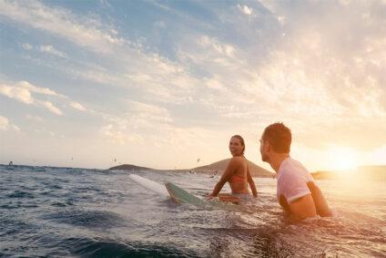 Zwei Surfer sitzen im Meer auf ihren Brettern.