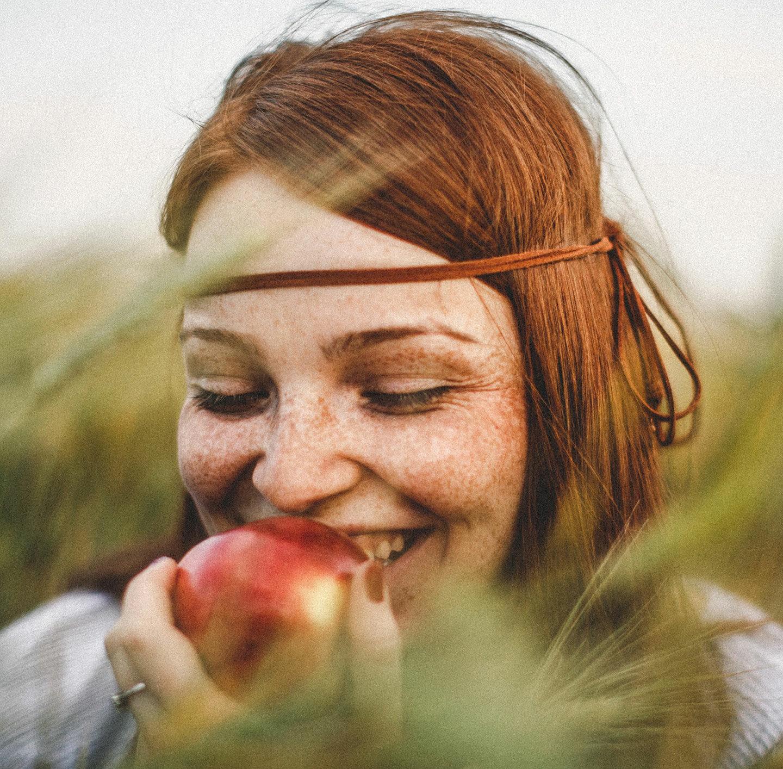 Frau mit roten Haaren steht in einem Feld und beißt in einen Apfel.