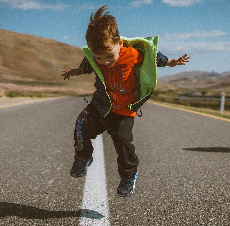 Kind spingt auf der Straße.
