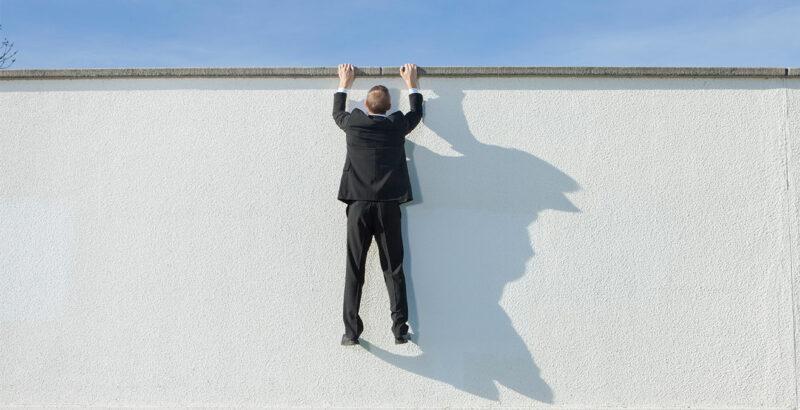 Ein Mann hängt an einer Mauer.