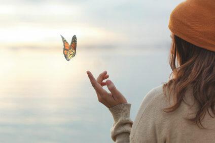 Ein Schmetterling landet auf dem Finger einer Frau.