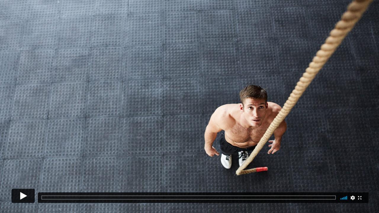 Sportler blickt auf ein langes Seil, das von der Decke hängt.