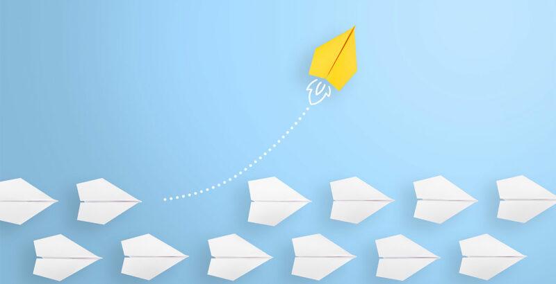Reihe weißer Papierflieger, ein gelber Papierflieger fliegt aus der Reihe.