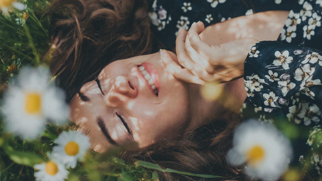 Frau auf einer Blumenwiese.