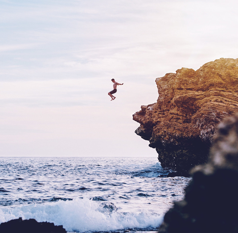 Mann springt von einer Klippe ins Meer.