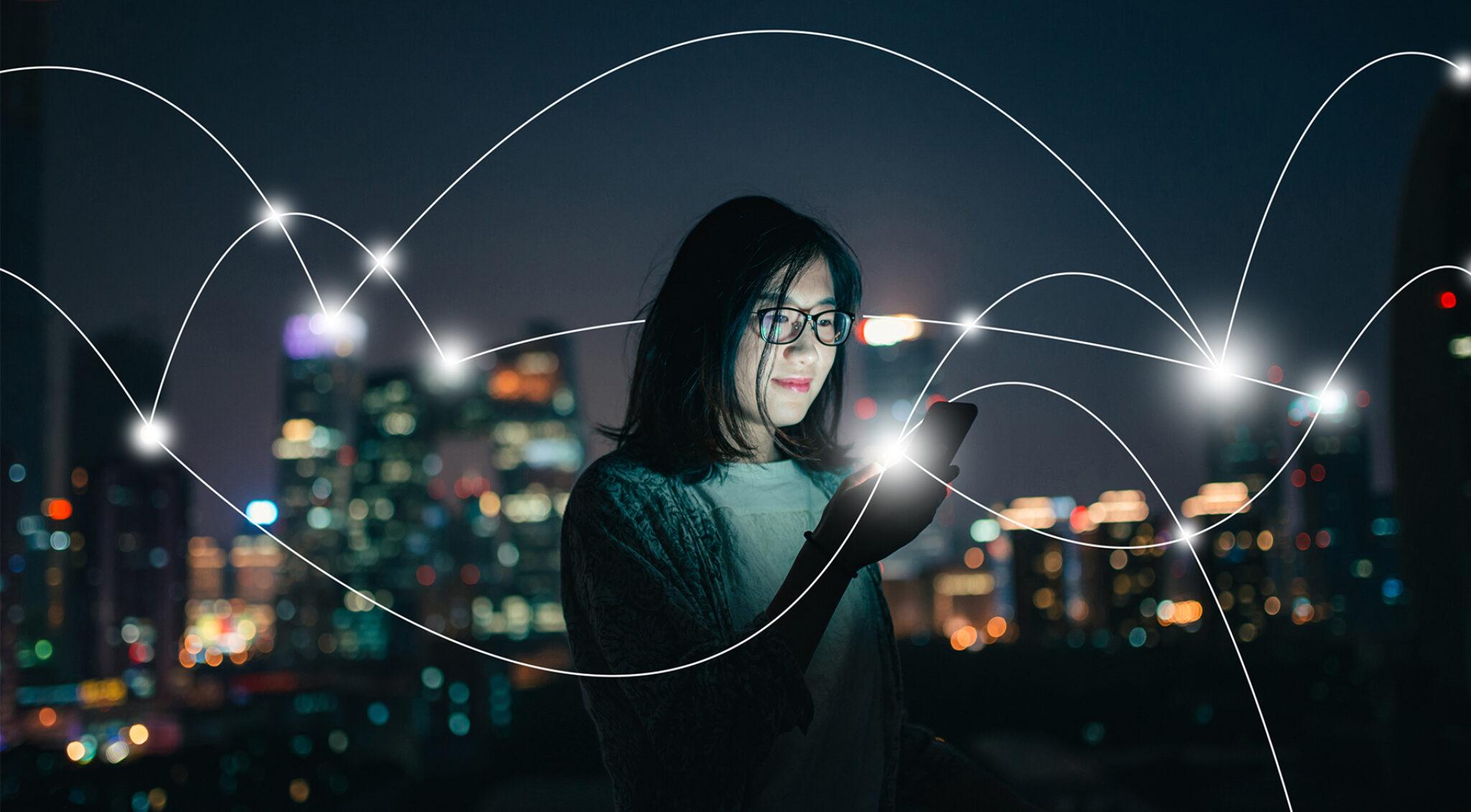 Junge Frau mit Handy vor beleuchteter Stadtkulisse.