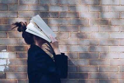 Frau hält sich ein Buch über das Gesicht.