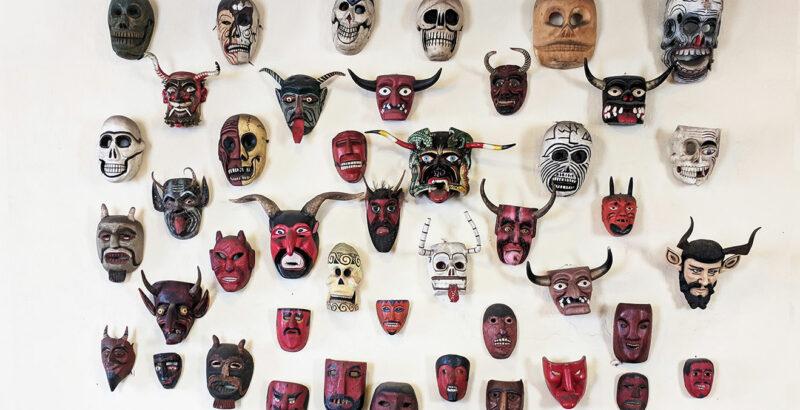 Volkstümliche Masken hängen an einer Wand.