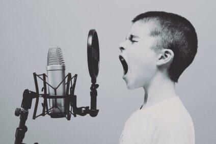 Ein Junge schreit in ein Mikrofon.