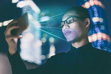 Chinesischer Mann blickt auf das Display seines Handys.
