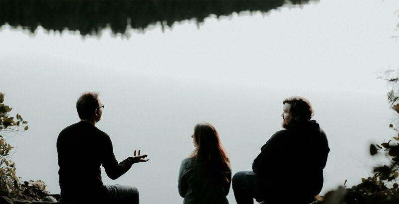 Drei Menschen sitzen in der Natur und unterhalten sich.