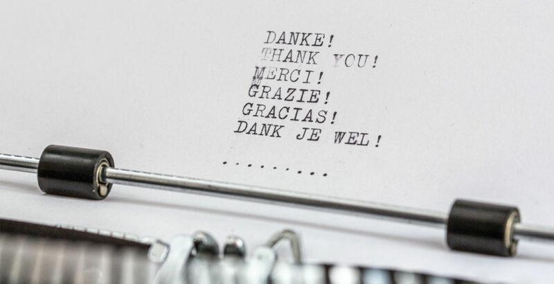 """Auf einer Schreibmaschine wurde das Wort """"Danke"""" in verschiedenen Sprachen getippt."""