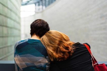 Frau legt ihren Kopf an die Schulter eines Mannes.