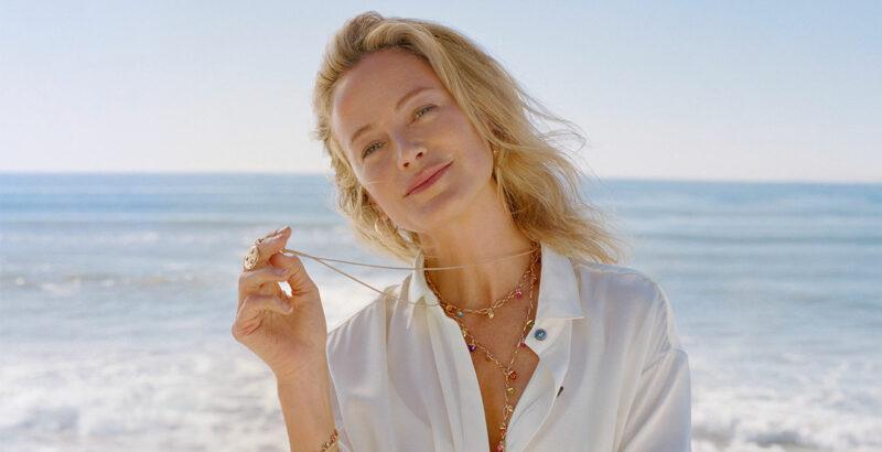 Blonde Frau am Strand trägt Ketten von Tamara Comolli.