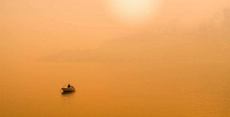 Boot auf dem Wasser vor Sonnenuntergang.